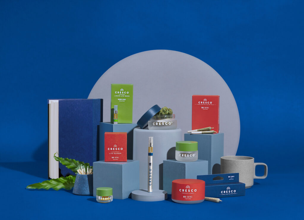 Cresco cannabis products on a blue table. There are vape pens, joints, and flower.